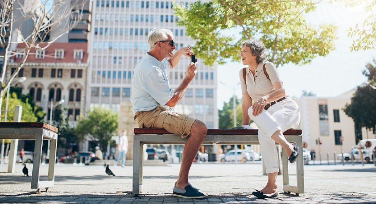 Senior man taking photos of his woman. Mature couple having fun on their holiday.